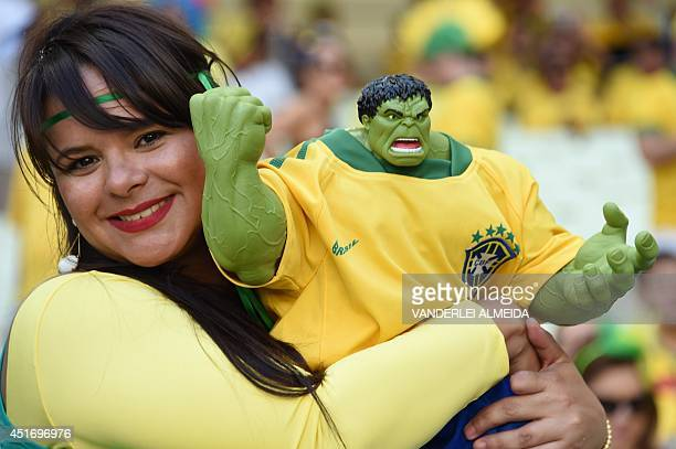 A fan of Brazil's forward Hulk holds a model of the Incredible Hulk before the quarterfinal football match between Brazil and Colombia at the...