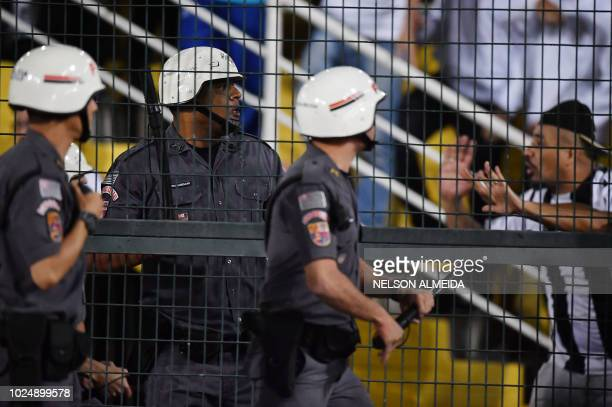 A fan of Brazil's Santos argues with riot police during the Copa Libertadores football match against Argentina's Independiente Pacaembu Stadium in...
