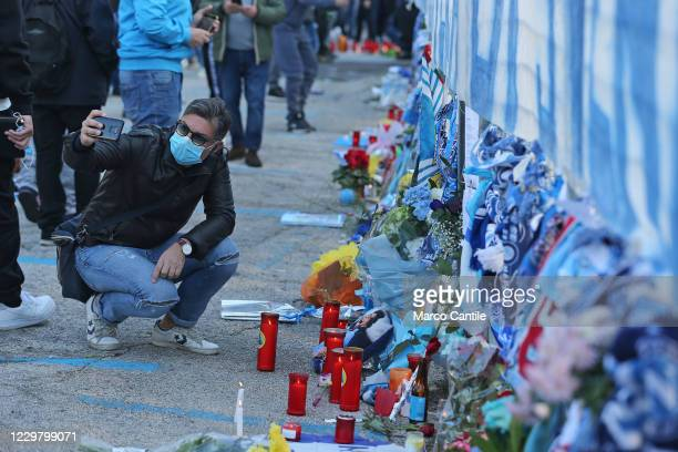 A fan of Diego Armando Maradona takes a selfie near the memorabilia and tealights left by fans in front of the San Paolo stadium in Naples the day...
