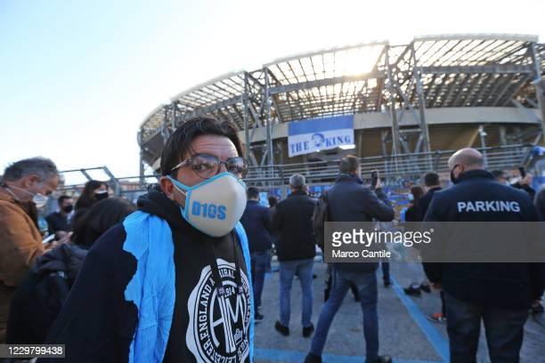 A fan of Diego Armando Maradona with a D10s mask in front of the San Paolo stadium in Naples the day after the death of the famous and legendary...