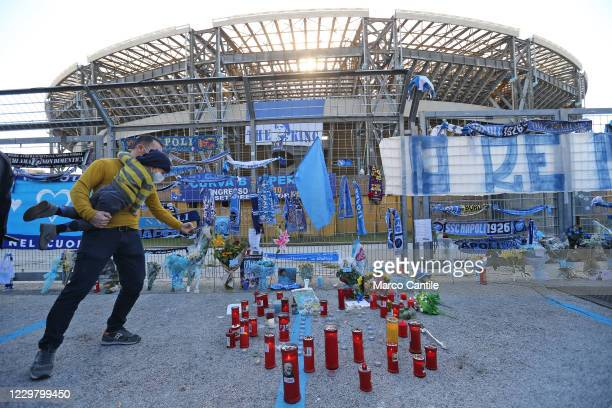 A fan of Diego Armando Maradona with his son takes a photo of the memorabilia and tealights left by fans in front of the San Paolo stadium in Naples...