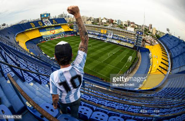 Fan of Diego Maradona raises his fist at the top of the stands of Alberto J. Armando stadium before a match between Boca Juniors and Newell's Old...
