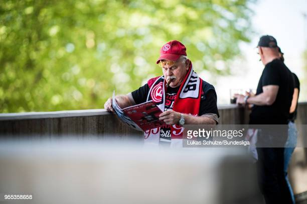 Fan of Duesseldorf poses with his cigar and reads the stadium magazin prior to the Second Bundesliga match between Fortuna Duesseldorf and Holstein...