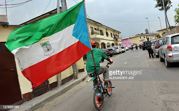 A fan of Equatorial Guinea's national football team rides a minibicycle on which he fixed his country's flag in the streets of Malabo on January 25...
