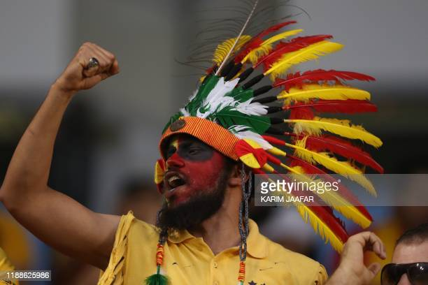A fan of Esperance de Tunis wearing a Native American war bonnet with feathers in his team's colours chants during the 2019 FIFA Club World Cup...