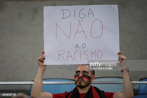 A fan of Flamengo holds a sign against racism before their Brazilian championship match against Gremio at Maracana stadium in Rio de Janeiro Brazil...