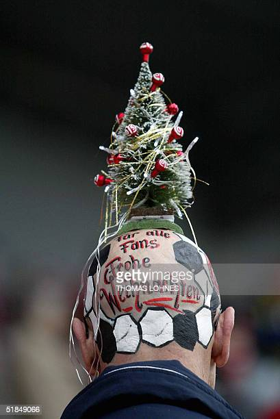 A fan of German first division football club Mainz wears a little Christmas tree on his painted bald head prior to the match of his club against...