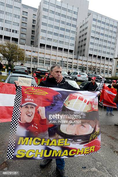 A fan of German Formula One world champion Michael Schumacher holds a giant poster showing pictures of the former pilot on January 3 in front of the...