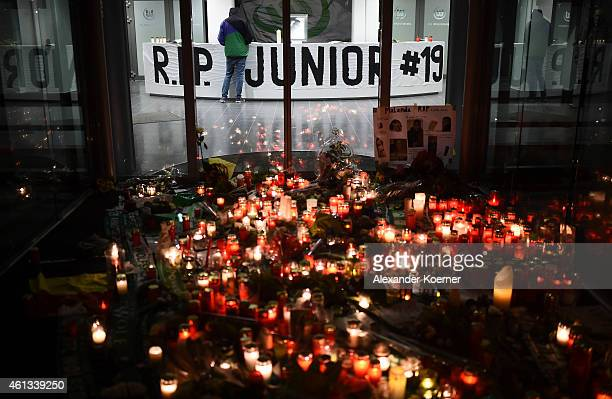 A fan of German soccer club VFL Wolfsburg stands inside the stadium behind candles and flowers at the entrance hall of VFL Wolfsburg stadium in...