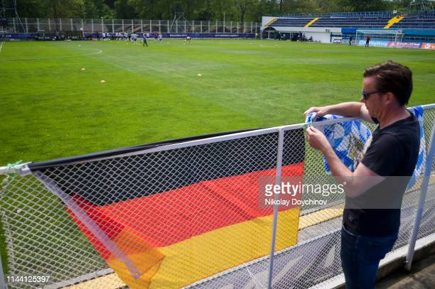A fan of Germany attaches a flags prior to the 2019 UEFA Women's Under17 EURO final match between Netherlands and Germany at Stadion Albena1 on May...