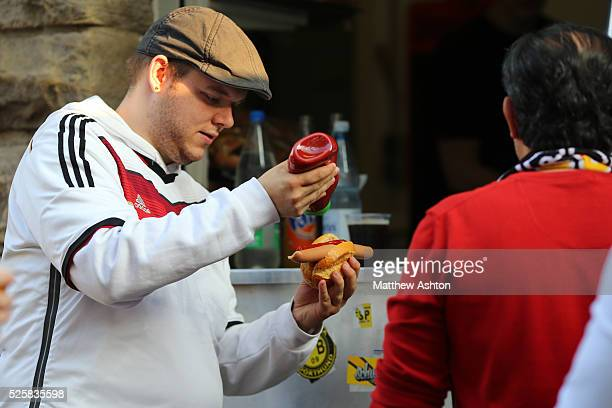A fan of Germany puts ketchup on his bratwurst sausage