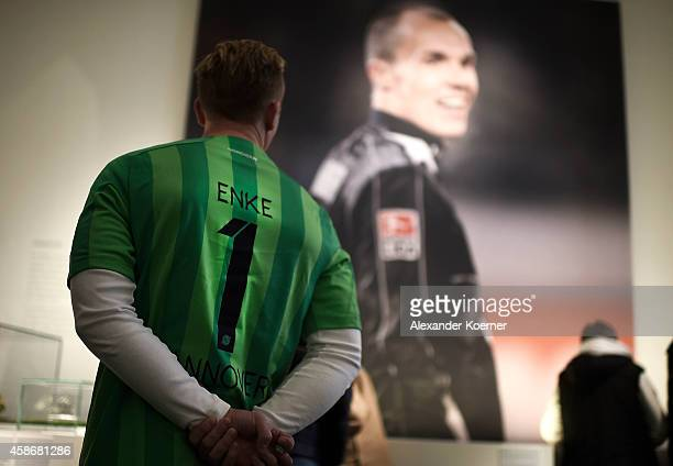 A fan of goalkeeper Robert Enke wearing a soccer jersey of Enke stands in front of a large billboard at the special exhibition ROBERT gedENKEn at...