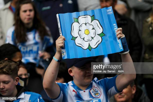 A fan of Huddersfield Town holds up a clapper with a Yorkshire Rose on during the Premier League match between Huddersfield Town and Tottenham...