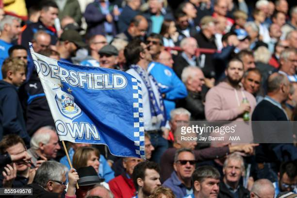 A fan of Huddersfield Town waves a flag during the Premier League match between Huddersfield Town and Tottenham Hotspur at John Smith's Stadium on...