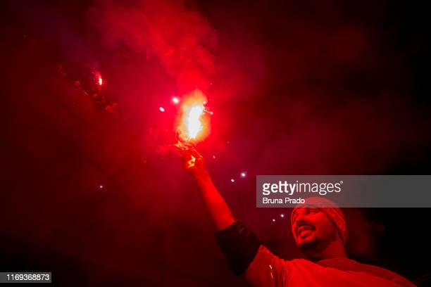 A fan of International light up a flare prior to a match between Internacional and Athletico PR as part of Copa do Brasil Final at BeiraRio Stadium...