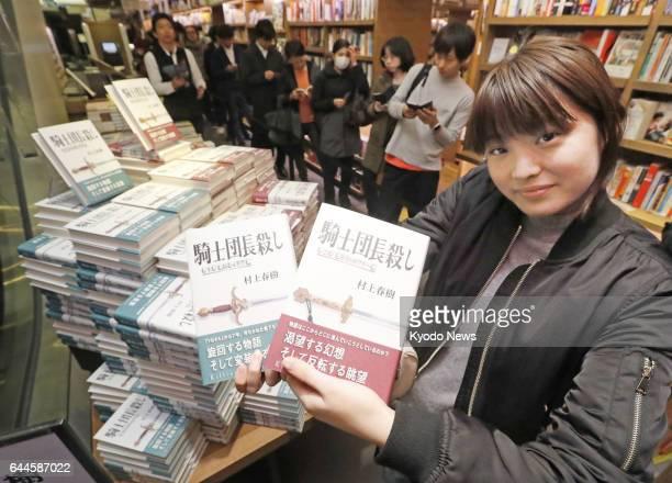 A fan of Japanese novelist Haruki Murakami shows copies of his first multivolume novel in seven years 'Kishidancho Goroshi ' at a Tokyo bookstore at...