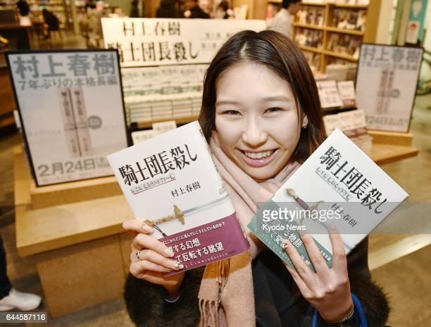 A fan of Japanese novelist Haruki Murakami shows copies of his first multivolume novel in seven years 'Kishidancho Goroshi ' at an Osaka bookstore at...