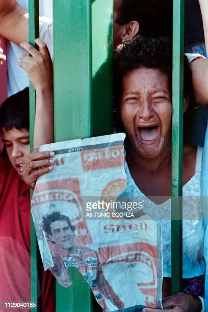 A fan of late Brazilian Formula One driver Ayrton Senna grieves while holding a picture of her idol on May 4 1994 as a motorcade carrying Senna's...
