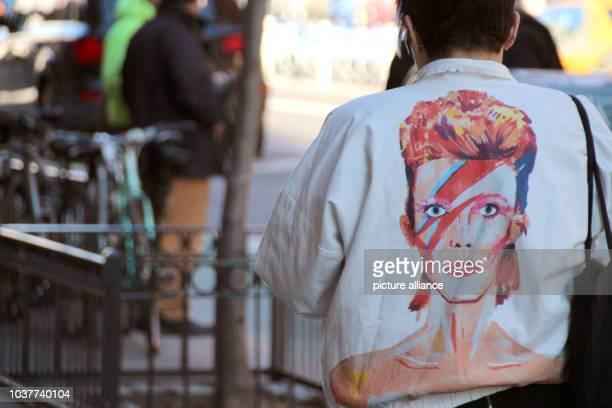 A fan of late British musician David Bowie wears a jacket featuring the cover of Bowie's 1973 album 'Aladdin Sane' in the SoHo district of New York...