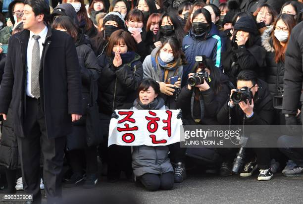A fan of late SHINee singer Kim JongHyun holds a banner reading Jong Hyun as the hearse carrying the body of Kim leaves from a hospital in Seoul on...