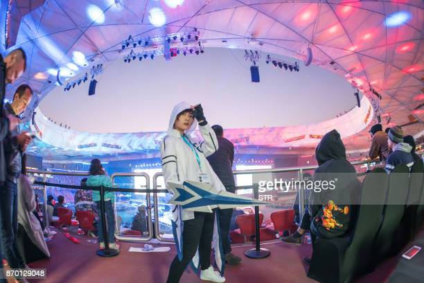 A fan of League of Legends in a cosplay outfit stands during the award cerenomy of the World Championships Final of League of Legends at the National...