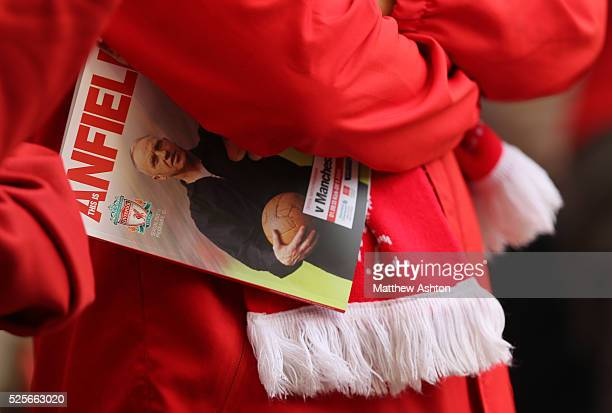 A fan of Liverpool holds a match day programme under his arm with Bill Shankly on the front cover