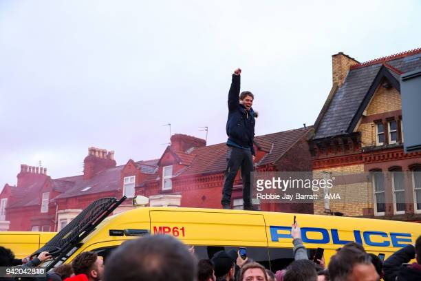 A fan of Liverpool stands on top of a Police van as fans await the team bus to arrive during the UEFA Champions League Quarter Final first leg match...