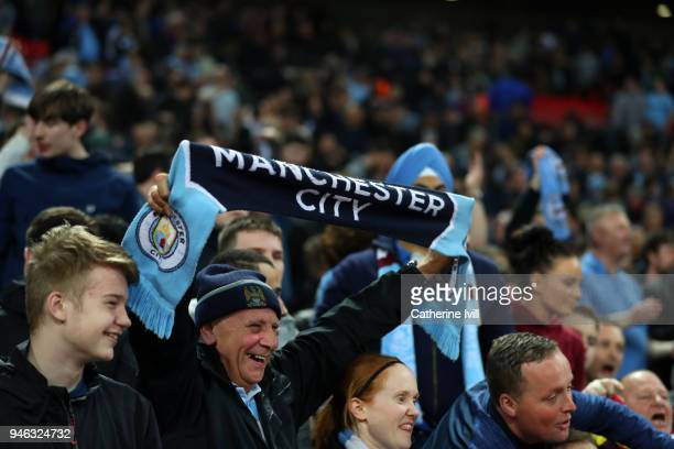 A fan of Manchester City holds up a scarf during the Premier League match between Tottenham Hotspur and Manchester City at Wembley Stadium on April...