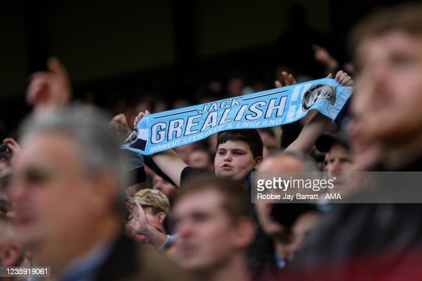 Fan of Manchester City holds up a scarf of Jack Grealish of Manchester City during the Premier League match between Manchester City and Burnley at...