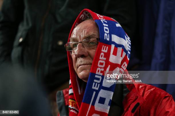 A fan of Manchester United shields himself from the rain with a scarf during the UEFA Champions League match between Manchester United and FC Basel...