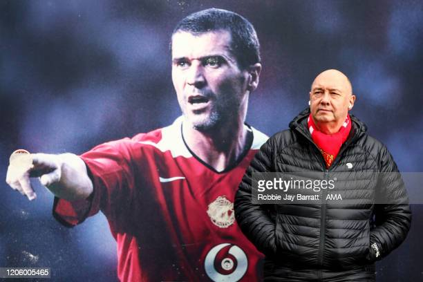 A fan of Manchester United stands in front of a giant poster of Roy Keane prior to the Premier League match between Liverpool FC and AFC Bournemouth...