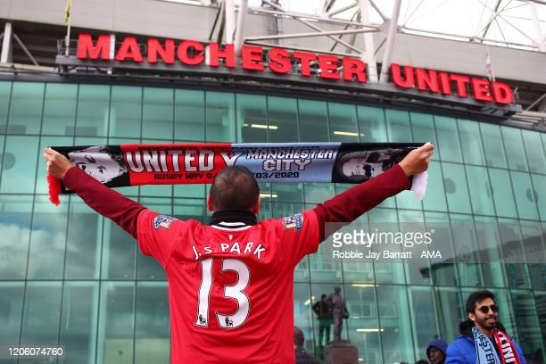 A fan of Manchester United wearing a shirt of Park Jisung holding up a bar scarf during the Premier League match between Manchester United and...
