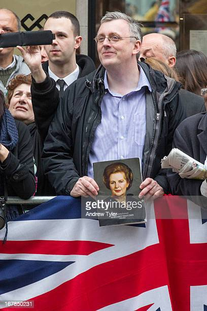 Fan of Margaret Thatcher eagerly waits to see her coffin pass on its way to St Paul's Cathedral for her funeral.