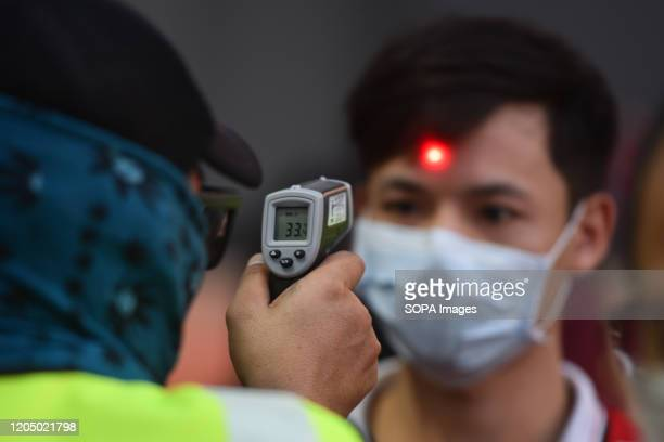Fan of Muangthong united has his temperature checked as a protective measure against corona virus during the Thai league match between Muangthong...