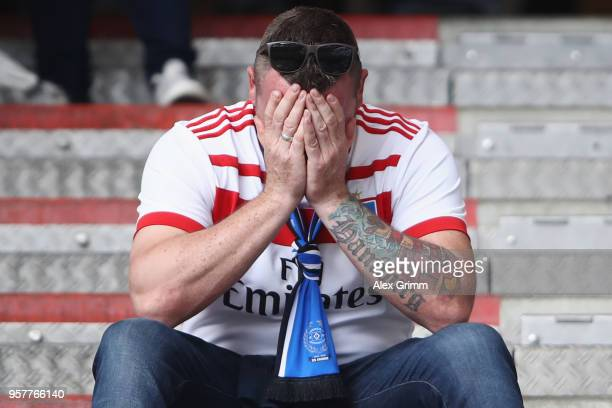 A fan of of Hamburg looks dejected after the Bundesliga match between Hamburger SV and Borussia Moenchengladbach at Volksparkstadion on May 12 2018...