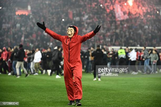 Fan of Olympiakos' sporting a Guy Fawkes mask enters the pitch after their UEFA Europa league match Olympiacos FC and AC Milan at the Karaiskaki...