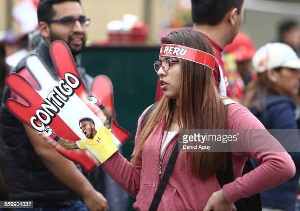 A fan of Peru holds a glove with the face of Pedro Gallese goalkeeper of Peru prior a match between Peru and Colombia as part of FIFA 2018 World Cup...