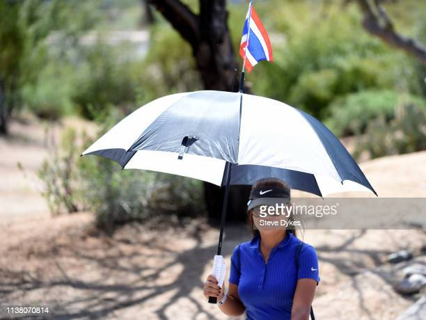 A fan of Pornanong Phatlum of Thailand Lucky Promkan carries an umbrella with the flag on Thailand attached as she follows her during the final round...