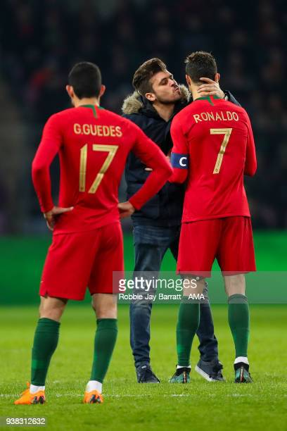 Fan of Portugal and Cristiano Ronaldo of Portugal runs on to the field to give Cristiano Ronaldo of Portugal a kiss during the International Friendly...
