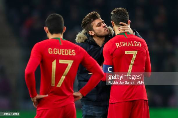 A fan of Portugal runs on to the pitch to give Cristiano Ronaldo of Portugal a kiss during the International Friendly match between Portugal and...