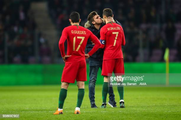 Fan of Portugal runs on to the pitch to give Cristiano Ronaldo of Portugal a kiss during the International Friendly match between Portugal and...