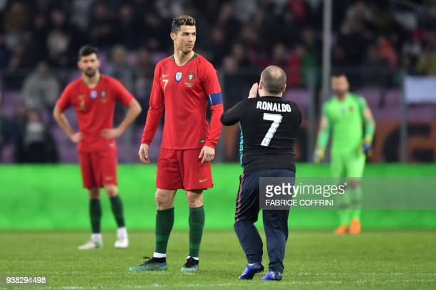 A fan of Portugal's forward Cristiano Ronaldo walks onto the pitch during the international friendly football match between Portugal and Netherlands...