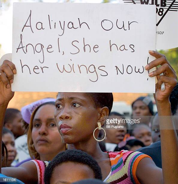 A fan of RB singer Aaliyah Haughton holds a sign during a memorial candlelight vigil August 27 2001 in Detroit Michigan at Aaliyah''s old school the...