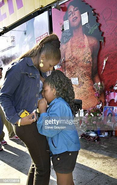 A fan of RB singer/actress Aaliyah is comforted by her motherafter viewing a record store mural of the late singer in what has a shrine dedicated to...