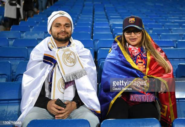 Fan of Real Madrid CF and a fan of FC Barcelona pose for a photograph prior to the La Liga match between Real Madrid CF and FC Barcelona at Estadio...