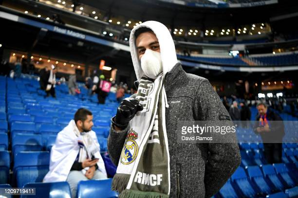Fan of Real Madrid CF wearing a face mask poses for a photograph prior to the La Liga match between Real Madrid CF and FC Barcelona at Estadio...