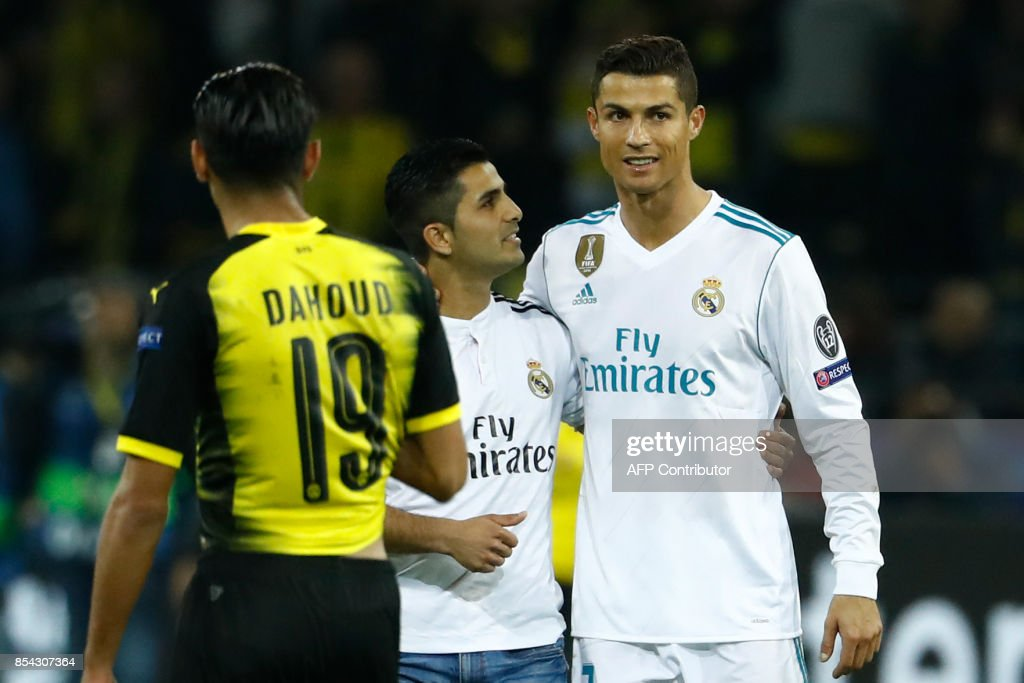 A fan (C) of Real Madrid's forward from Portugal Cristiano Ronaldo (R) embraces his hero after the UEFA Champions League Group H football match BVB Borussia Dortmund v Real Madrid in Dortmund, western Germany on September 26, 2017. / AFP PHOTO / Odd ANDERSEN