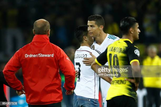 A fan of Real Madrid's forward from Portugal Cristiano Ronaldo embraces his hero after the UEFA Champions League Group H football match BVB Borussia...