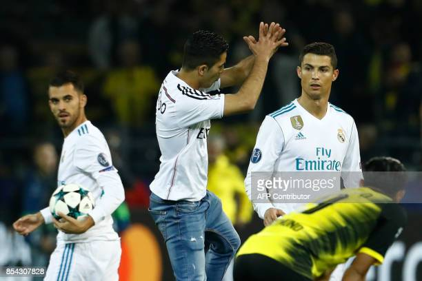A fan of Real Madrid's forward from Portugal Cristiano Ronaldo jumps next to his hero after the UEFA Champions League Group H football match BVB...