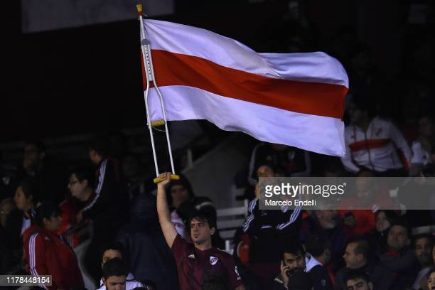 A fan of River Plate waves a flag with a crutch prior to the semi final first leg match between River Plate and Boca Juniors as part of Copa CONMEBOL...